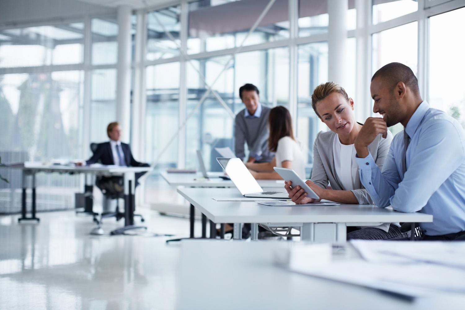 Business colleagues discussing over digital table at office desk