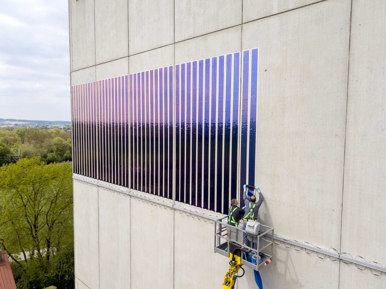 workers applying solar film to building