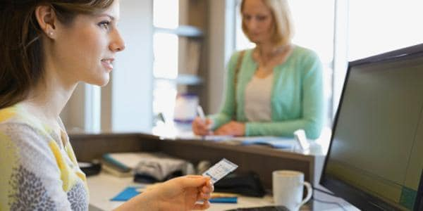 Young woman working in medical office with insurance card and patient