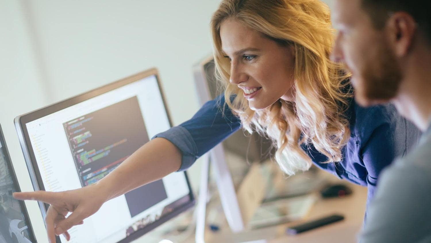 Man Working on Computer and woman pointing on screen