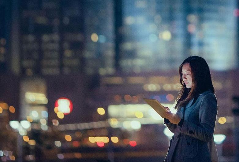woman using tablet at dusk in the city