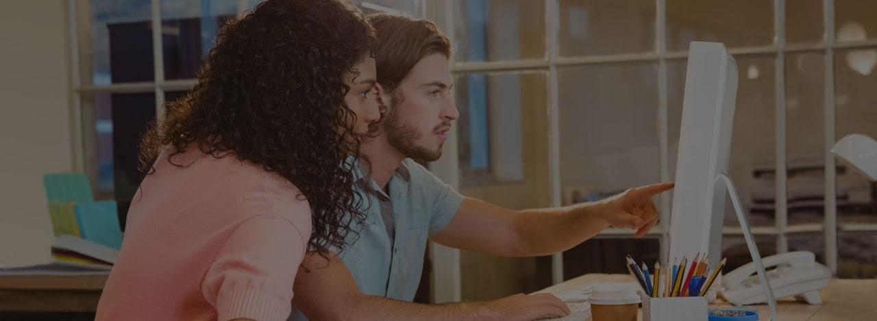 ชายหนุ่มและหญิงสาวกำลังทำงานด้วยกันหน้าคอมพิวเตอร์แล็ปท็อป