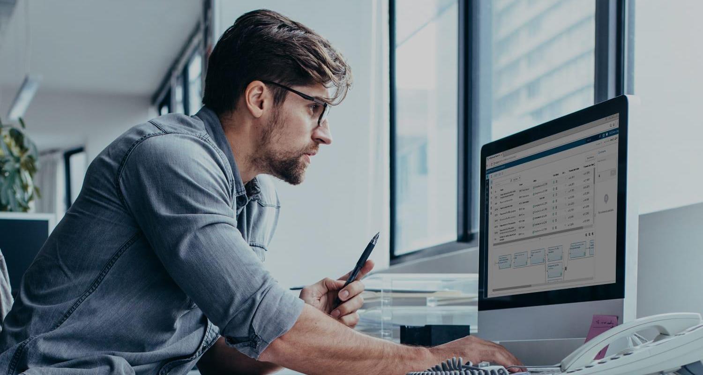 Young businessman reviews data on desktop computer