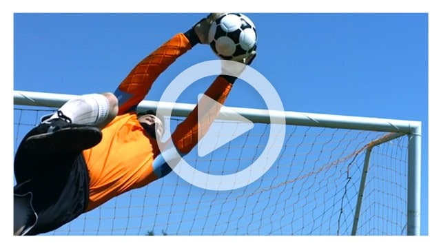 Player catching ball over net in soccer game