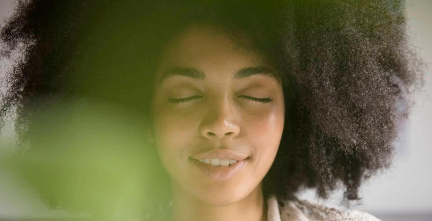 African American woman closing eyes and smiling