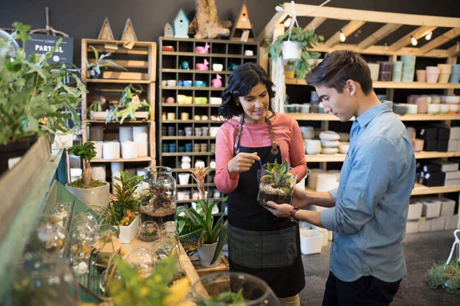Female shop owner helping male customer shopping in plant shop