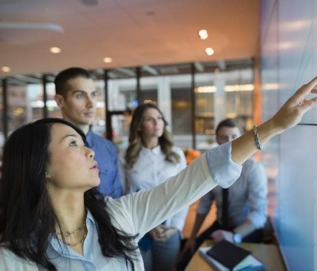 Group of coworkers in conference room having discussion with woman pointing at screen
