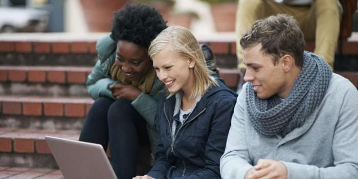 Three students collaborating on a laptop on outside stairs