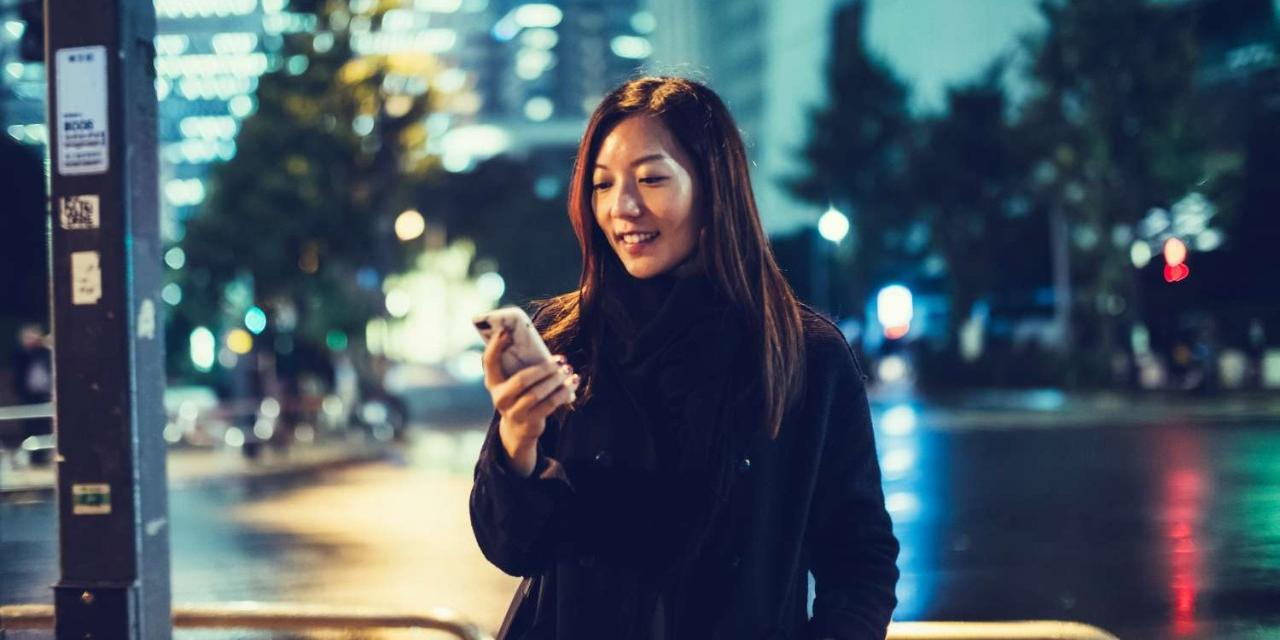 Young Japanese Asian Woman Downtown Tokyo At Night Using Smartphone