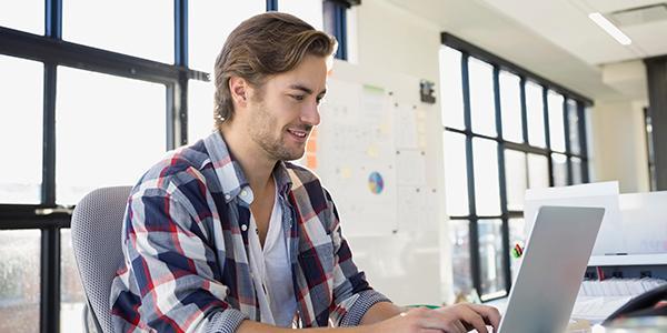 坐在桌子前使用笔记本电脑工作的男性