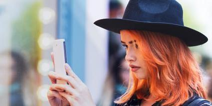 young woman with red hair and hat taking a selfie while shopping