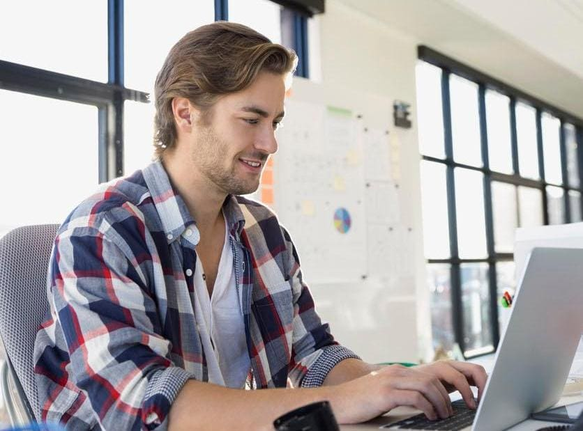坐在办公椅上使用笔记本电脑工作的男性