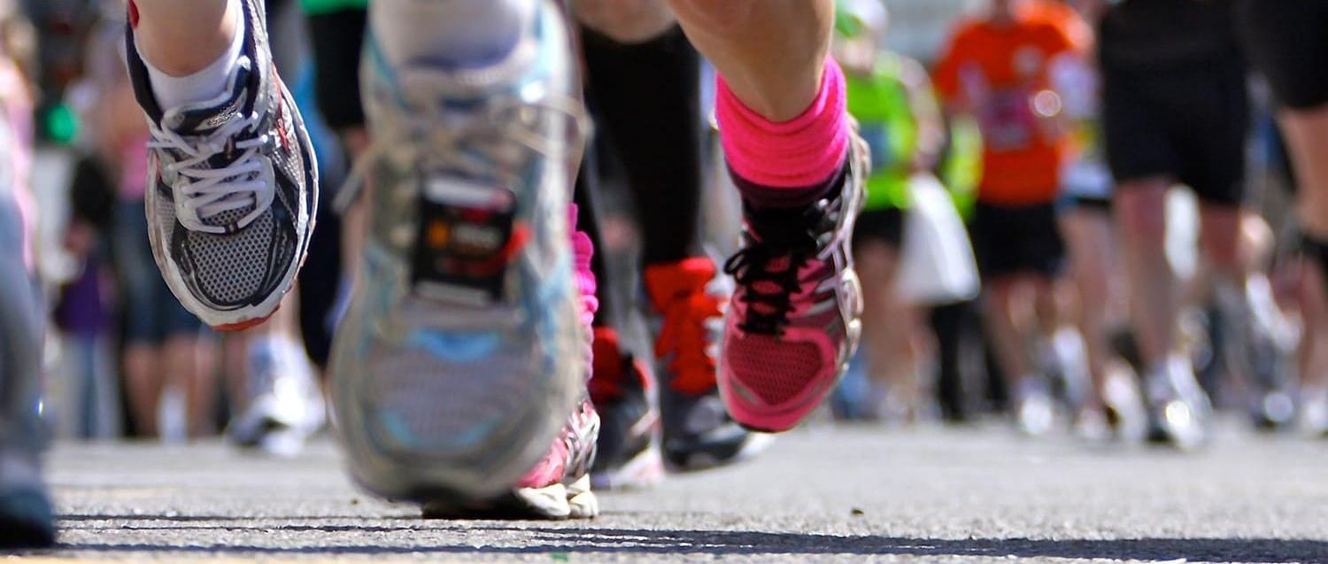 Close up of several peoples' running shoes