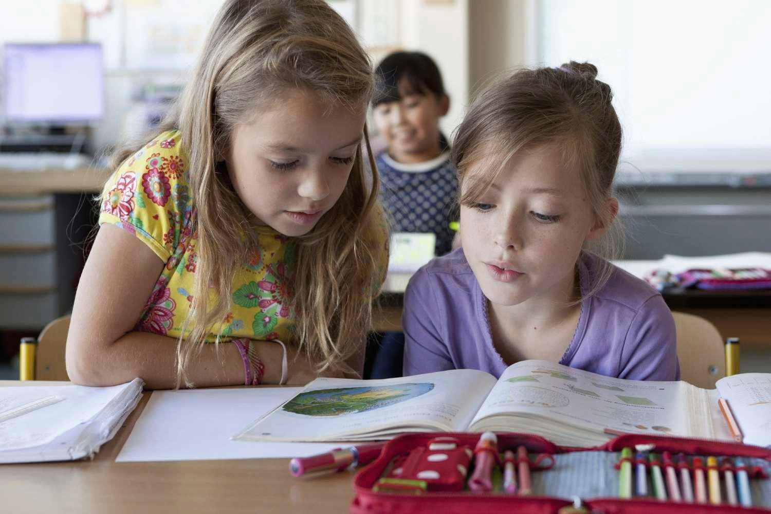 Two young female students reading a book together in a classroom