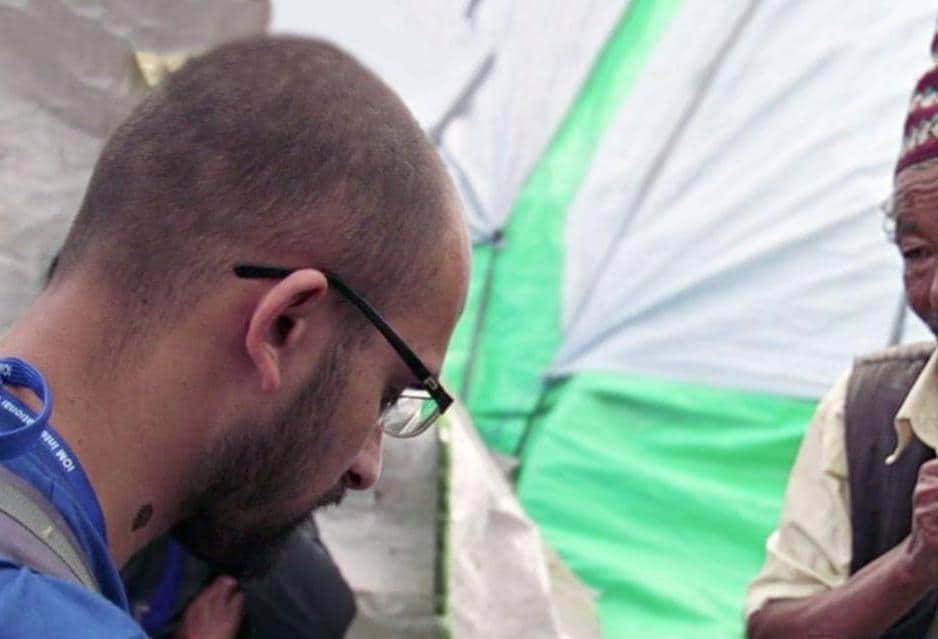 IOM Worker Speaking to Man By Shelters