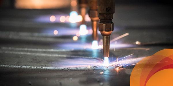 Orange spirograph superimposed on closeup of manufacturing welders