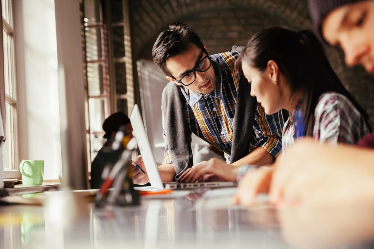Man with glasses and asian woman discussing next to a computer screen