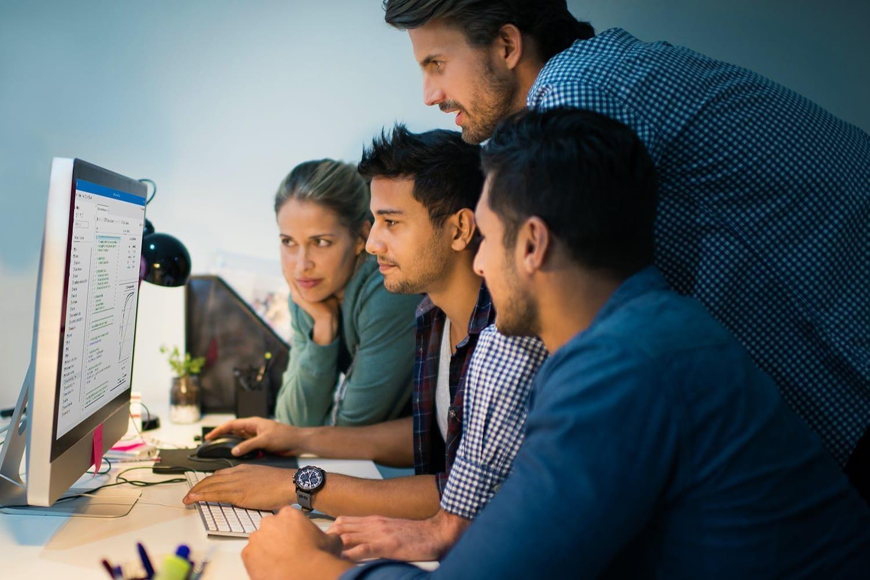 Employees gather around desktop computer
